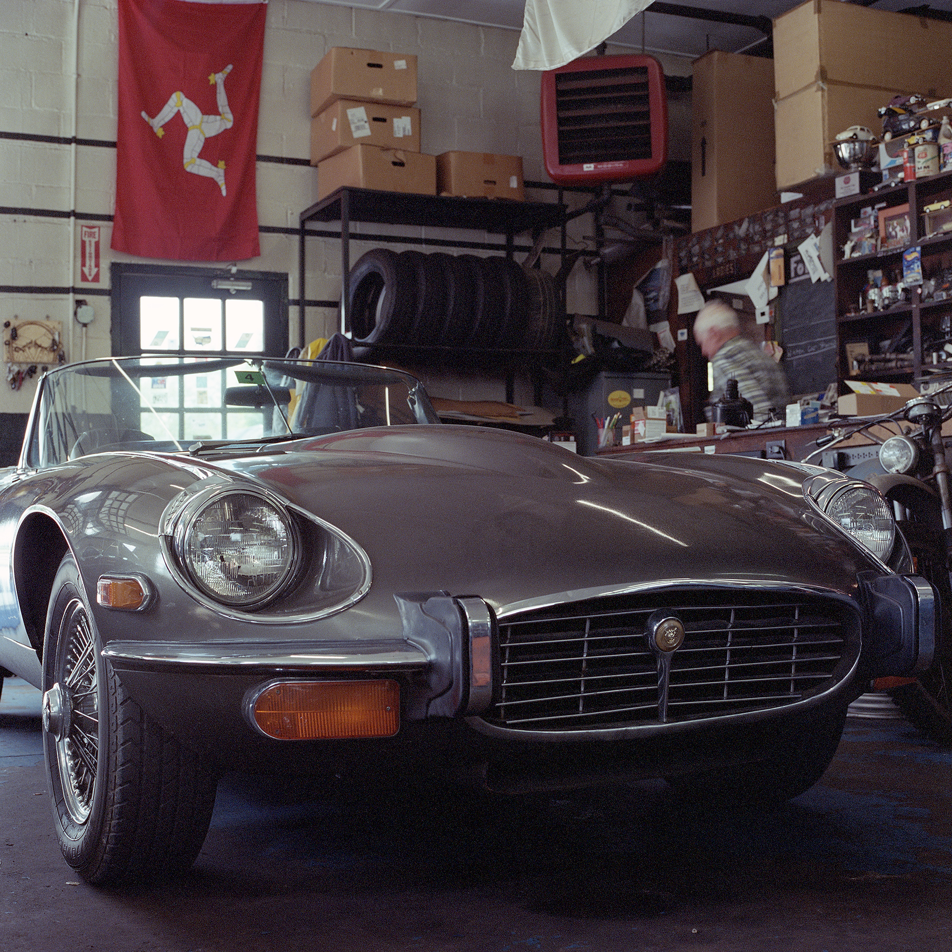 Color photo of low angle shot of grey Jaguar E-Type and Ava Restoration Services