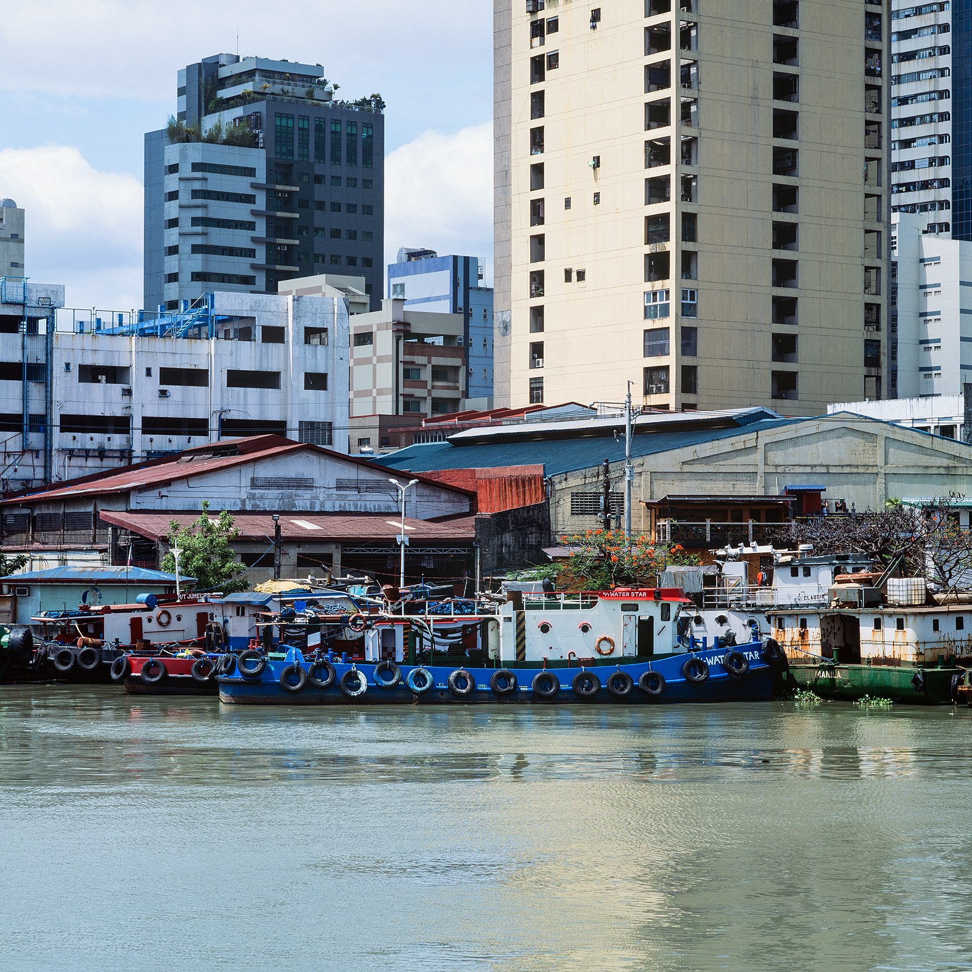 Tugboats moored on the side of the Pasig River