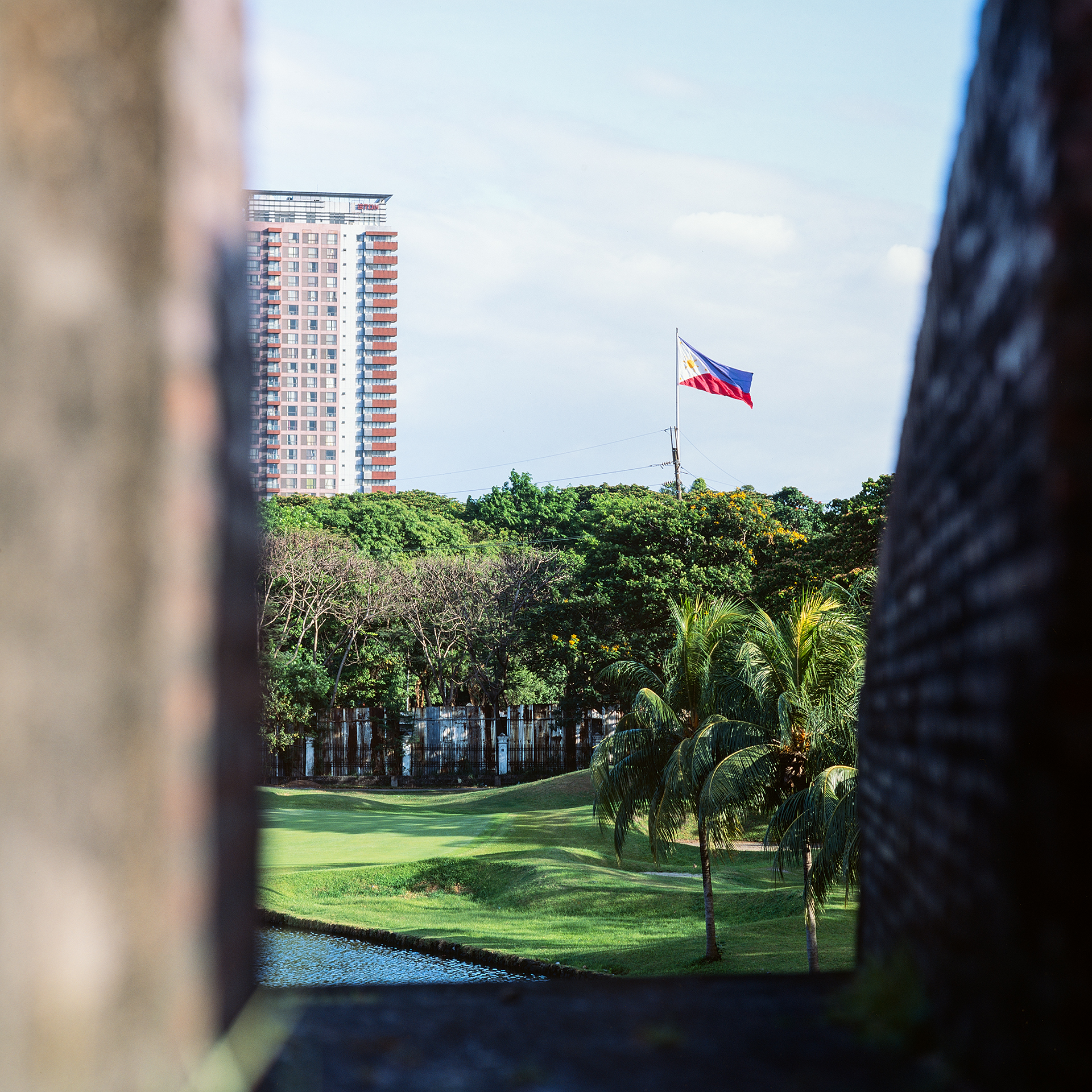 Looking out of the wall at Baluarte De San Diego at the Philippines flag