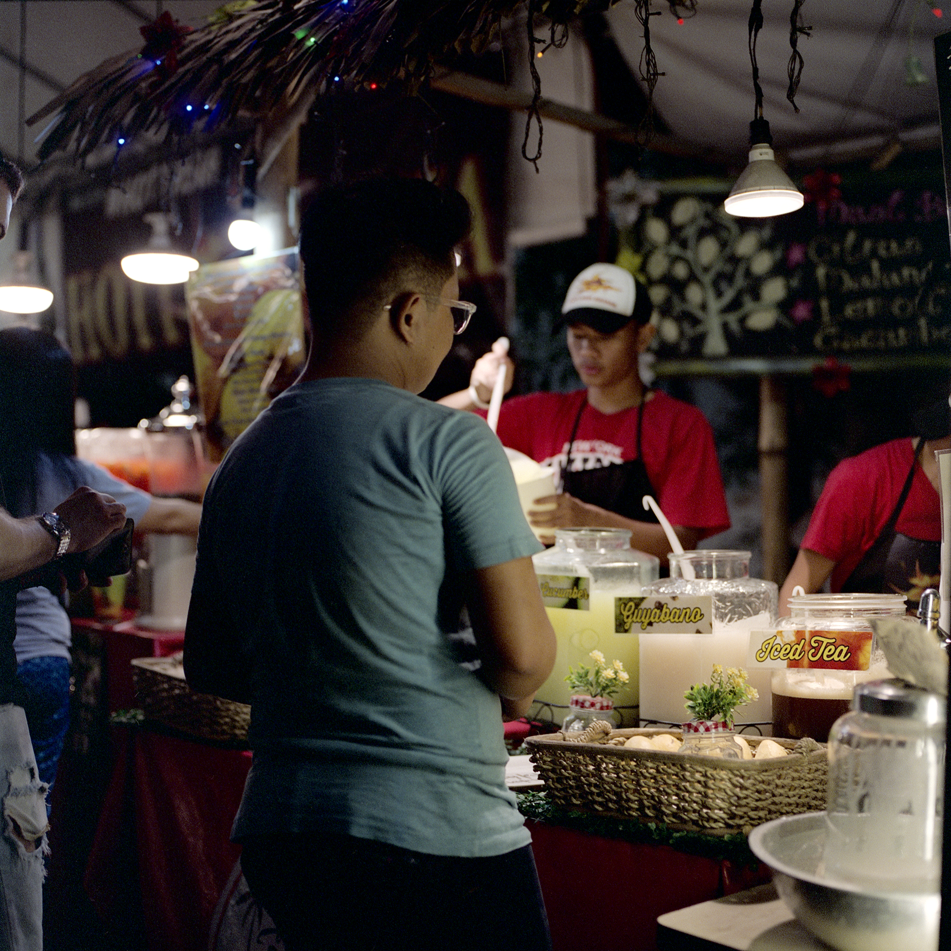 People getting different kinds of juices at a night market