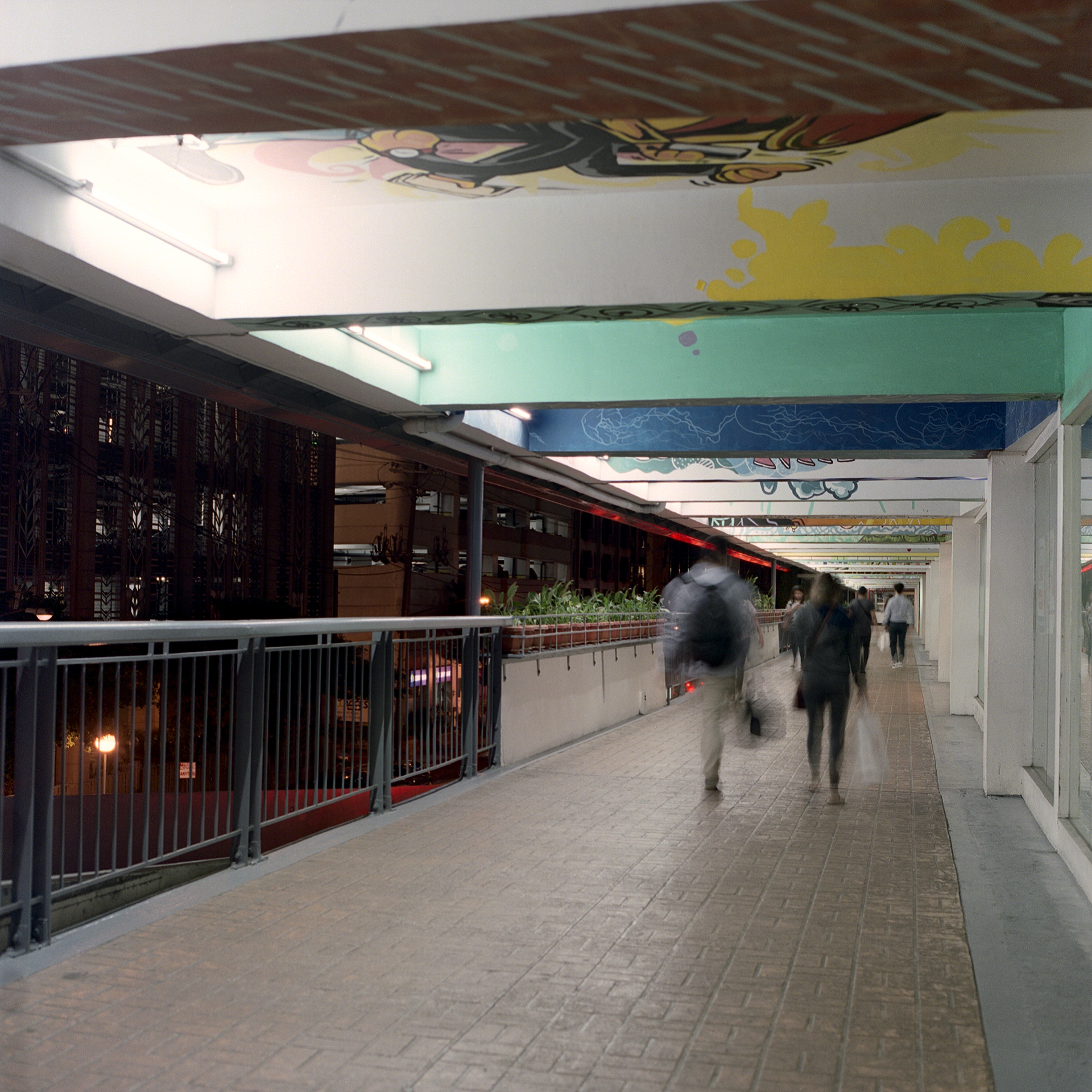 A pedestrian bridge going to the mall in Makati that has art painted by different artists all across the ceiling of the walkway